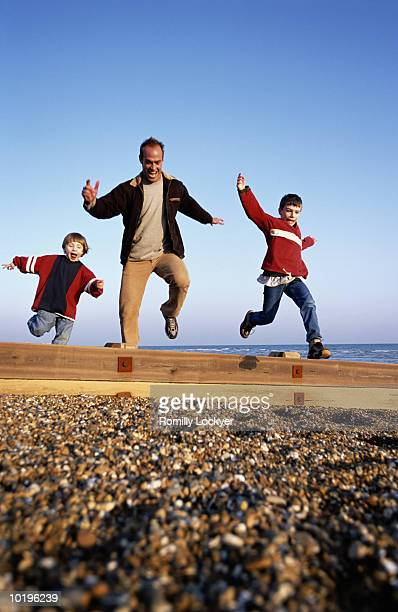 Father and sons (5-10) jumping over beach groyne