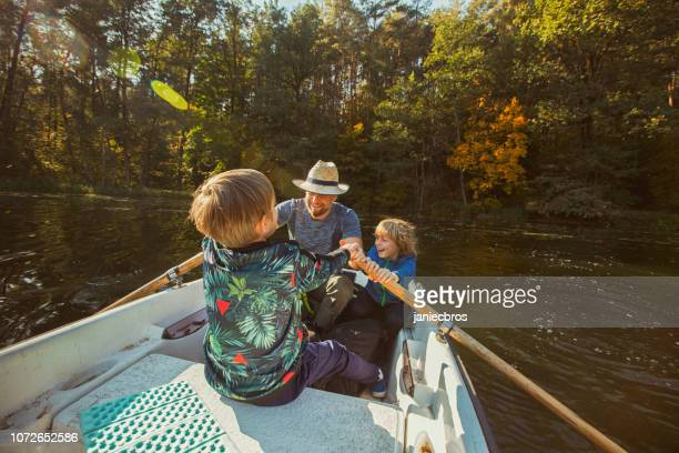 father and sons kayaking on a lake - masculinity stock pictures, royalty-free photos & images