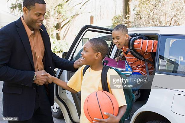 Father and sons leaving car