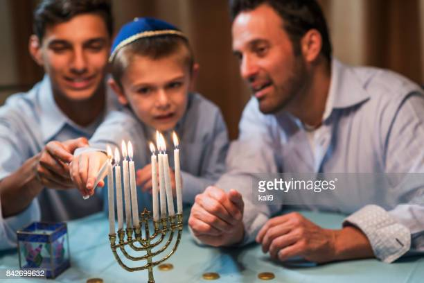 father and sons lighting menorah - menorah stock photos and pictures