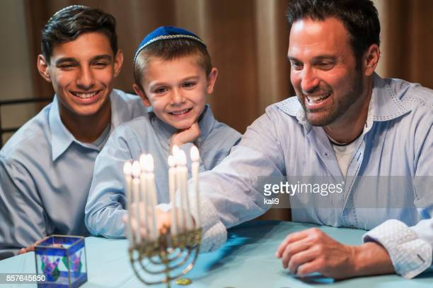 father and sons lighting menorah - hanukkah imagens e fotografias de stock