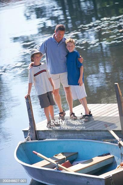 father and sons (8-11) on dock - sandaal stockfoto's en -beelden