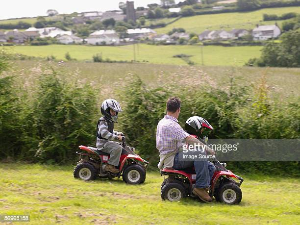 Father and sons on quad bikes