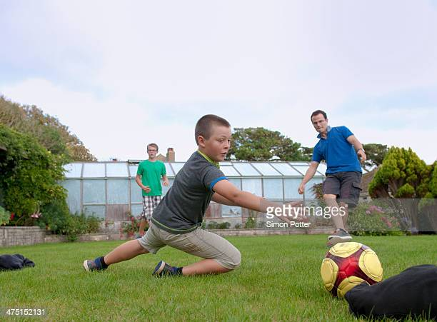 Father and sons playing football in garden