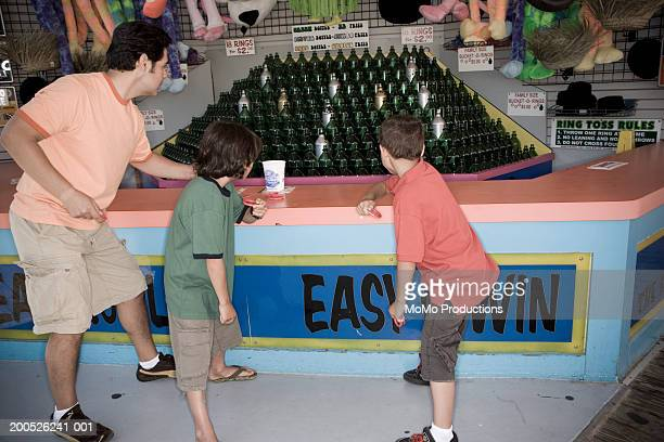 Father and sons (5-9) playing ring toss at boardwalk, rear view
