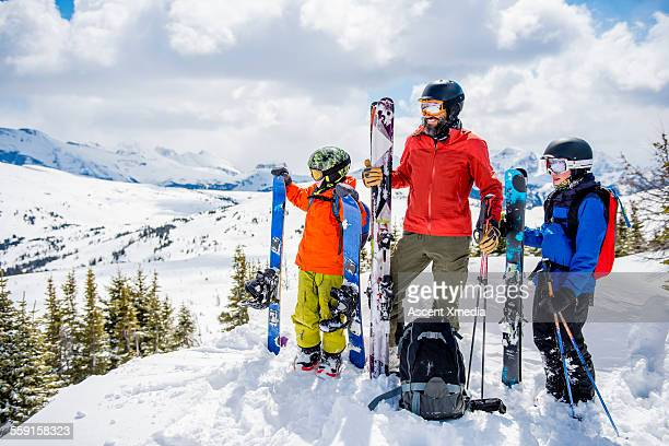 father and sons relax in fresh snow, with skiis - ski holiday stock photos and pictures