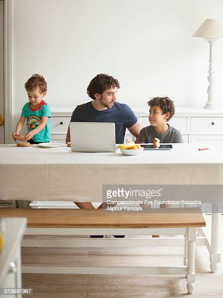 Father and sons relaxing in dining room