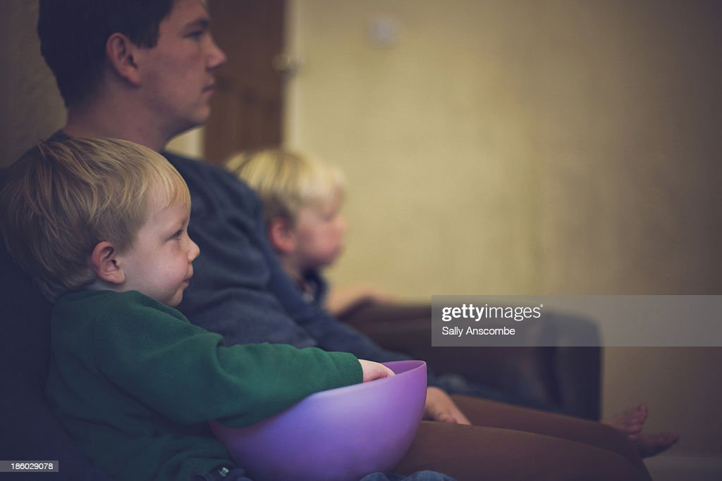 Father and sons sitting on the couch together : Stock Photo