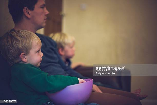 Father and sons sitting on the couch together