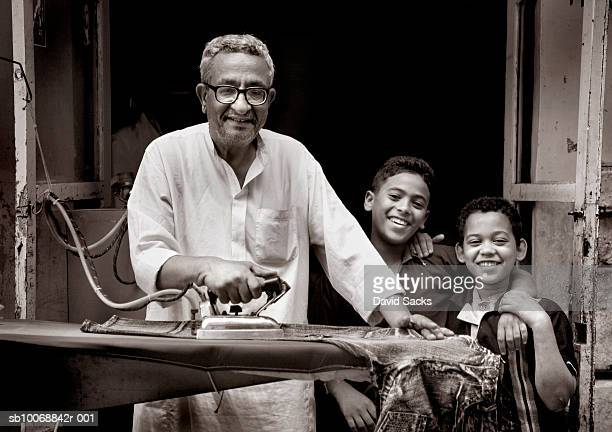 Father and sons (6-10) smiling over ironing board, portrait