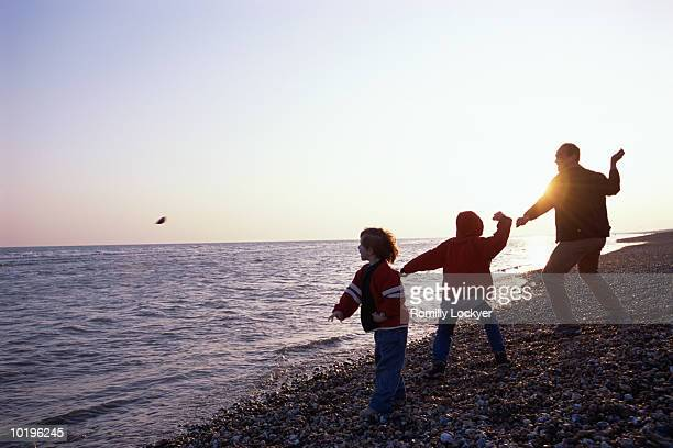Father and sons (5-10) throwing stones into ocean at sunset