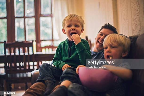 Father and sons watching television together