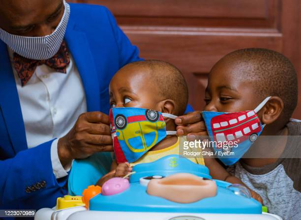 father and sons wearing face masks - africa stock pictures, royalty-free photos & images