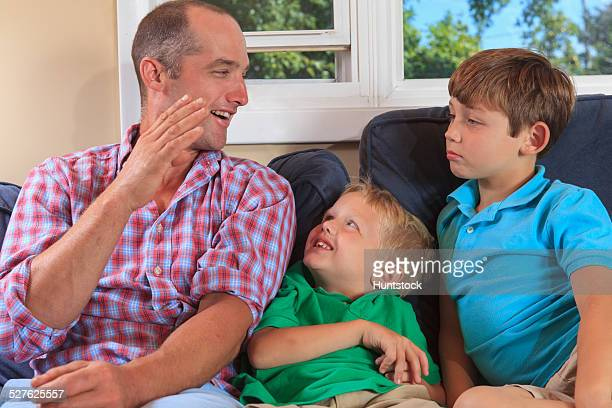 Father and sons with hearing impairments signing B in American sign language on their couch