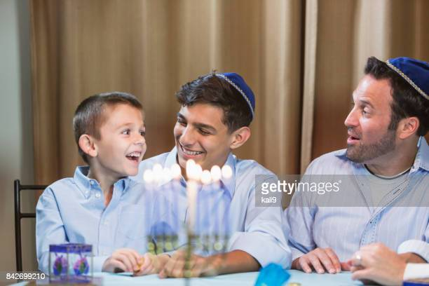 father and sons with menorah - jewish man stock photos and pictures