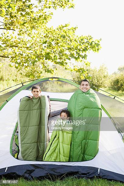 Father and Sons Wrapped in Sleeping Bags In Tent