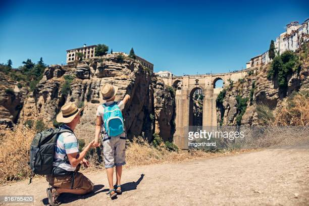 father and sun admiring puente nuevo in ronda, spain - andalucia stock pictures, royalty-free photos & images