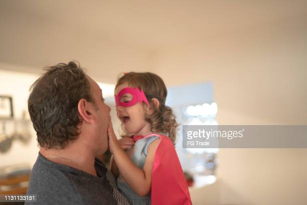 father and superhero daughter embracing at home - superhero stock pictures, royalty-free photos & images