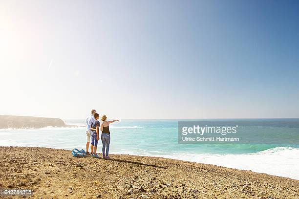 Father and teenage children overlooking open sea