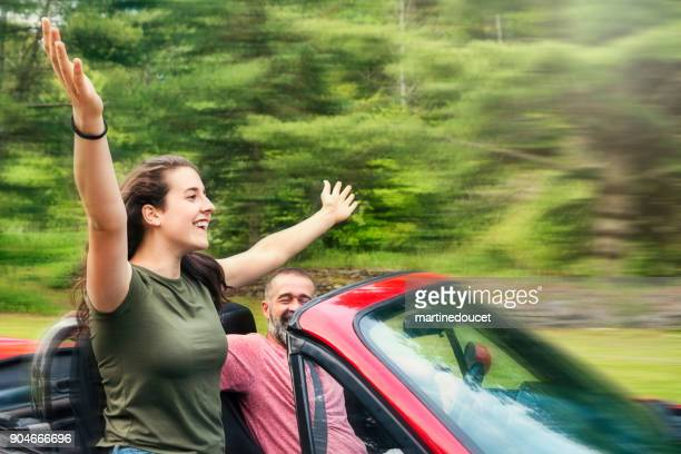 Father and teenage daughter enjoying a ride in red convertible car.
