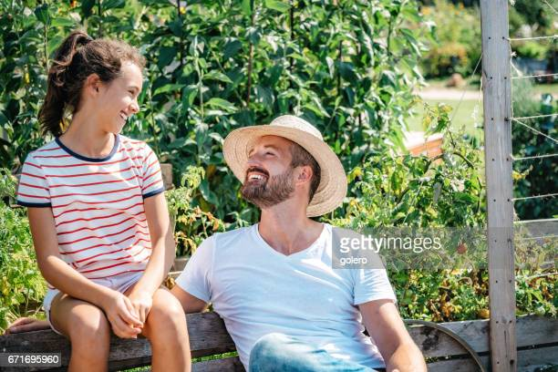 father and teenage daughter having fun in summer garden
