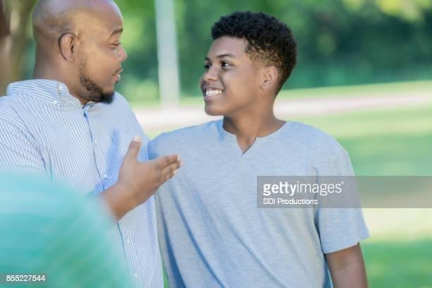 Padre y el hijo adolescente disfrutan de conversación al aire libre de la vinculación
