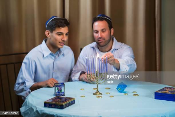 Father and teenage son lighting menorah