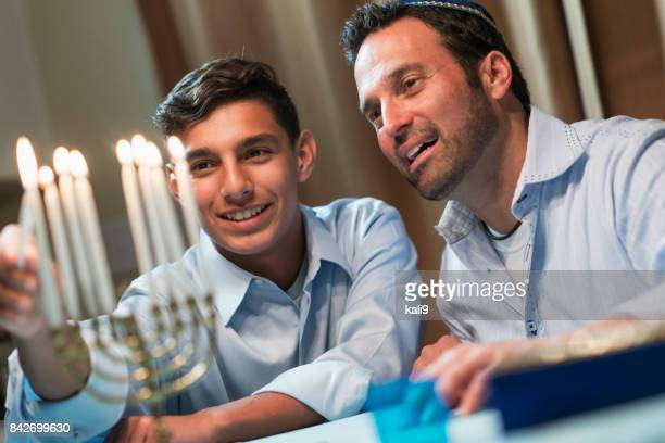 father and teenage son lighting menorah - hanukkah imagens e fotografias de stock