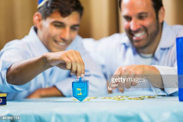 father and teenage son playing dreidel - dreidel stock photos and pictures