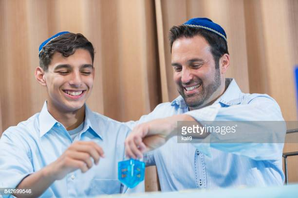 Father and teenage son playing dreidel