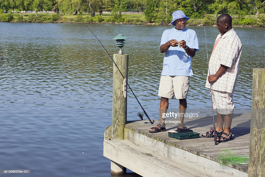 Father and teenage son (13-14) standing on jetty with fishing rods : Foto stock