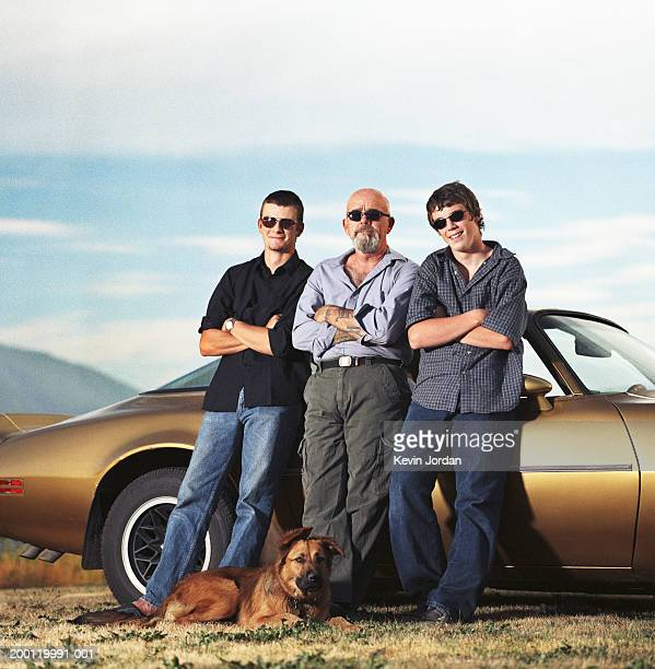 father and teenage sons (12-17) leaning against sports car, portrait - best sunglasses for bald men stock pictures, royalty-free photos & images