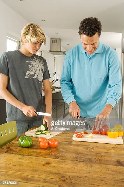 Father and teenager cooking, indoors