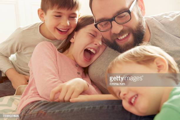 Father and three children laughing together