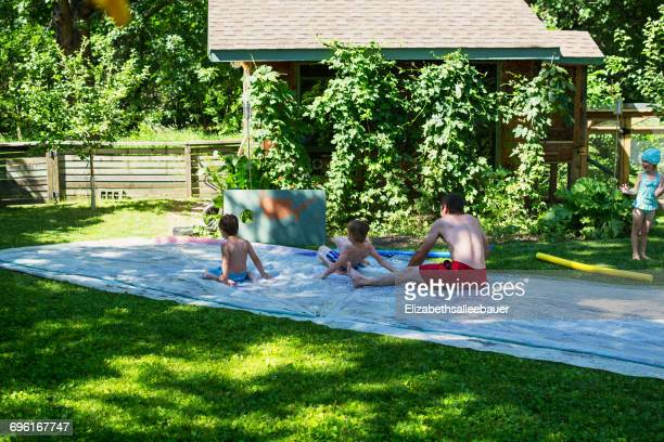 Father and three children playing on a slip and slide in the garden