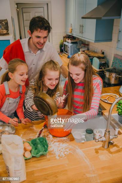 Father and Three Daughters Pouring the Ingredients into a Bowl