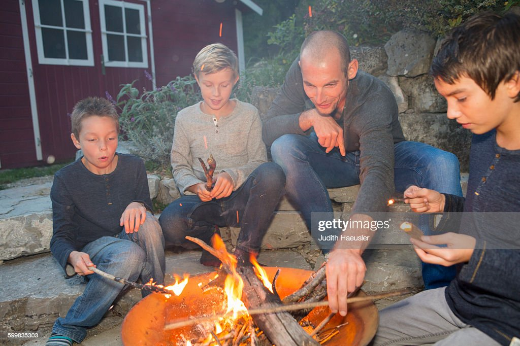 Father and three sons sitting by garden campfire at dusk : Stock Photo