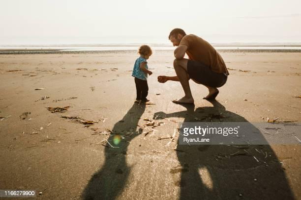 vader en peuter leeftijd dochter op sandy ocean beach - alleenstaande vader stockfoto's en -beelden