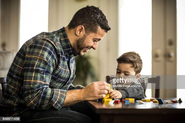 Father and toddler boy (2 yrs) playing with blocks