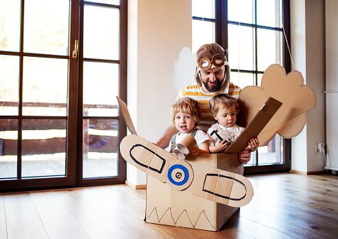 A father and toddler chidlren playing with carton plane indoors at home. 1153595586