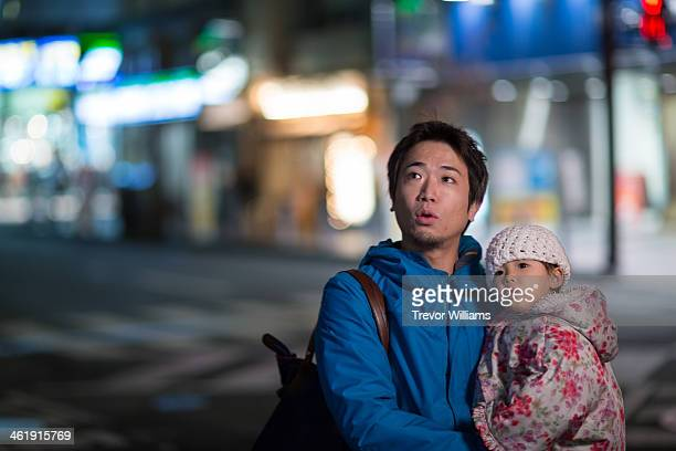 Father and toddler daughter in city at night