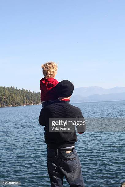 Father and toddler daughter looking at view across lake