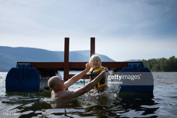 father and toddler daughter playing in lake, silver bay, new york, usa - lake george new york stock pictures, royalty-free photos & images
