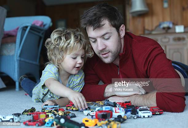 Father and toddler daughter playing with toy cars in sitting room
