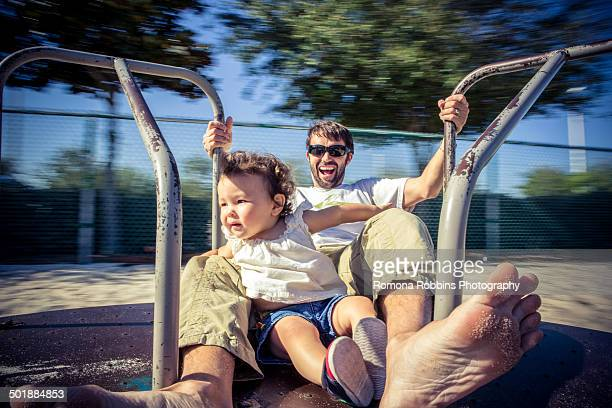 Father and toddler daughter spinning on park roundabout