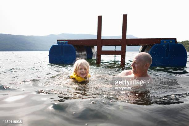 father and toddler daughter swimming in lake, silver bay, new york, usa - heshphoto stock pictures, royalty-free photos & images