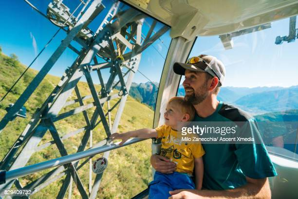 Father and toddler look out cable car window