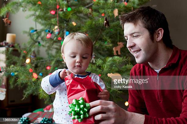 Father and toddler son opening Chrstmas gift.