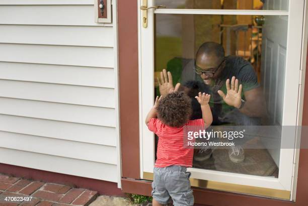 Father and toddler son playing at screen door