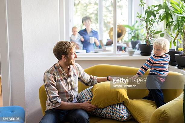 Father and toddler son playing on sofa.